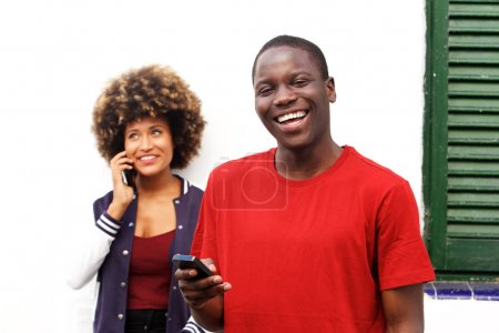Close up portrait of happy man smiling with mobile phone and woman making a phone call in background