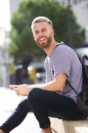 Portrait of smiling male university student sitting outside with mobile phone