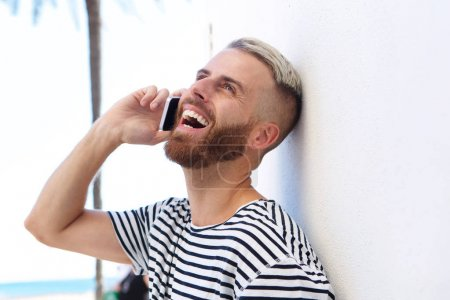 Side portrait of cool young guy laughing and talking on cell phone