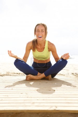 Portrait of young woman in yoga pose at the beach and laughing