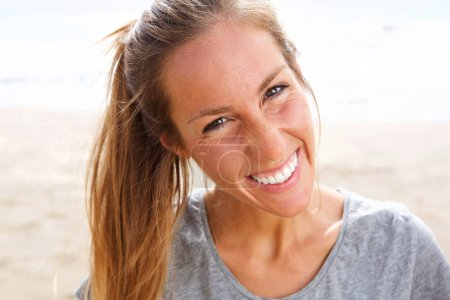 Close up portrait of attractive young woman laughing by the beach