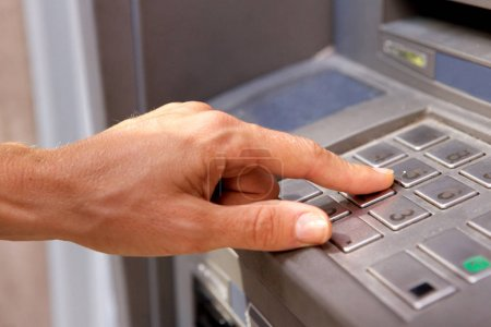 cropped closeup image of female hand using bank machine keypad