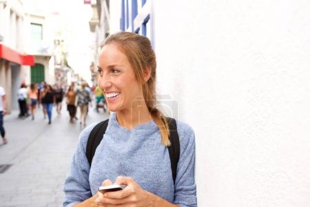 Portrait of young attractive woman with mobile phone in the city