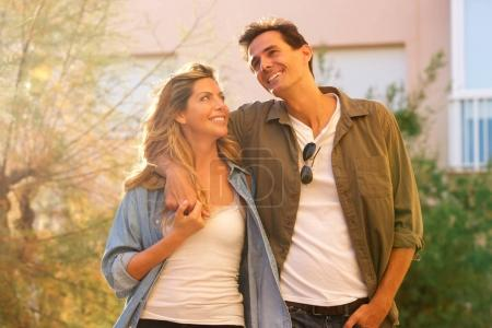 Portrait of laughing couple walking together on date in embrace