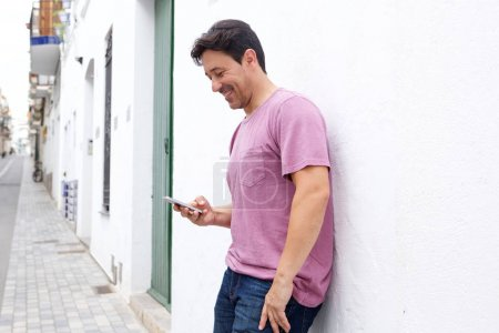 Portrait of middle aged man standing outside and reading text message on his mobile phone