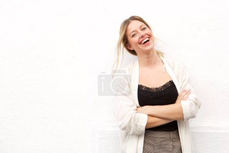 Portrait of young woman laughing against white wall