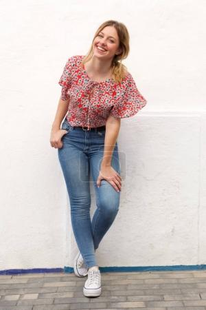 Photo for Full length portrait of smiling young blond woman in jeans against white wall - Royalty Free Image