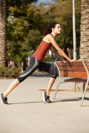 Full body portrait of healthy young sports woman stretching outdoors