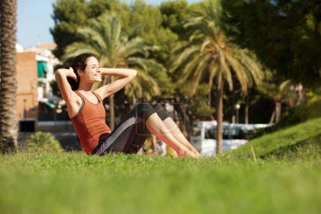 Portrait of active young woman doing sit ups outdoors