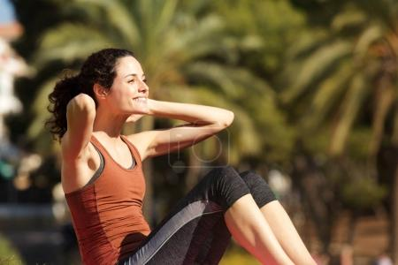 Portrait of smiling woman doing sit ups in park