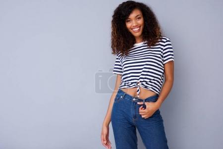 Portrait of happy young woman smiling in striped shirt against gray background