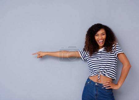 Portrait of happy young black woman smiling and pointing against copy space on gray background