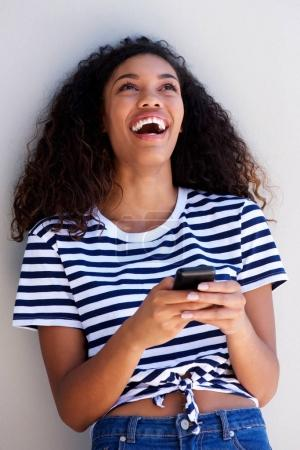 Portrait of young woman laughing with cellphone