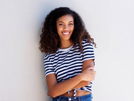 Portrait of confident young black woman smiling against white wall