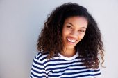 Close up horizontal portrait of beautiful young african woman smiling against white wall