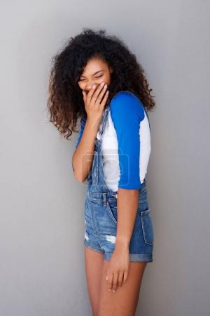 Photo for Portrait of happy young african american woman giggling against gray wall - Royalty Free Image