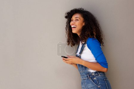 Side portrait of happy young african woman laughing with cellphone against gray background
