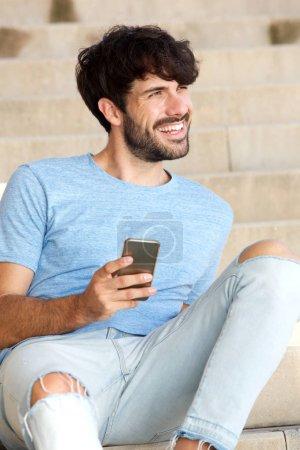 Retrato de joven guapo sentado con teléfono inteligente