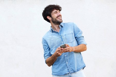 Portrait of cool handsome man with beard holding mobile phone