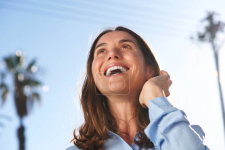 Close up portrait of happy  woman laughing Wirth hand in hair outside