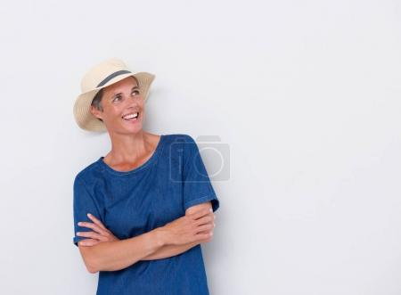 Portrait of smiling middle age woman against white wall with hat