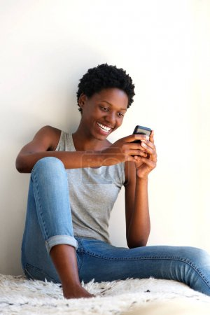 Portrait of smiling african woman relaxing at home and looking at smart phone