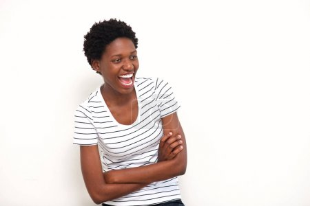 Portrait of happy young african american woman laughing with arms crossed on white background