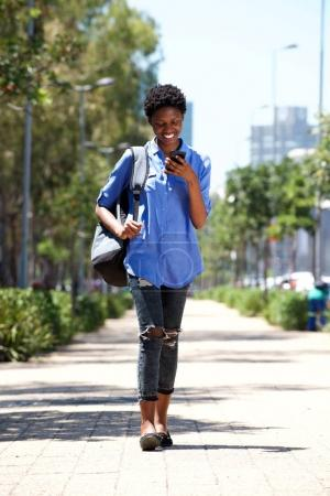 Full length portrait of young woman walking down the street with cellphone