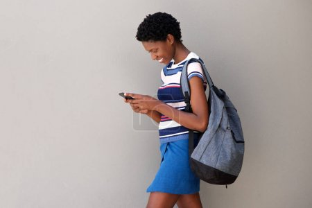 Side portrait of young woman walking with bag and using smart phone on gray background