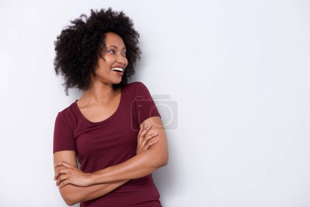 Portrait of smiling woman standing with arms crossed by white wall