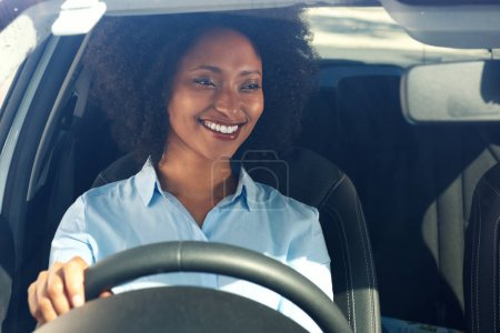 Portrait of happy young african american woman driving a car and smiling