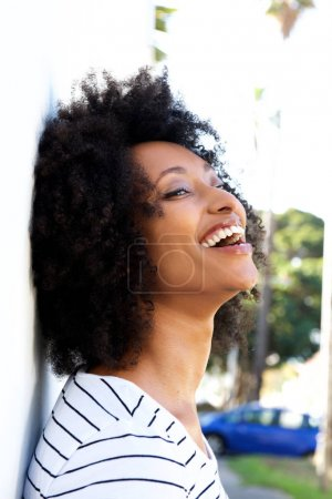 Close up portrait of african woman with curly hair leaning to wall outdoors and smiling