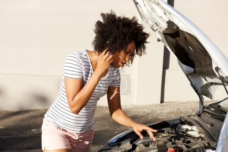 Photo for Portrait of young african woman standing by broken down car parked on the road and calling for assistance - Royalty Free Image