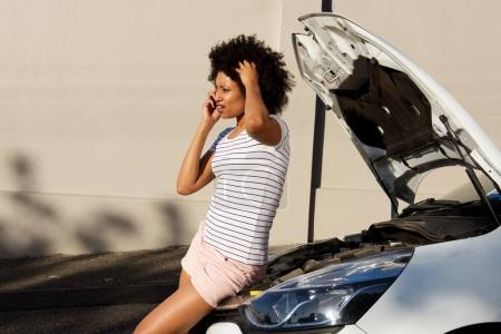 Photo for Side portrait of young woman standing by broken down car and making phone call for assistance - Royalty Free Image