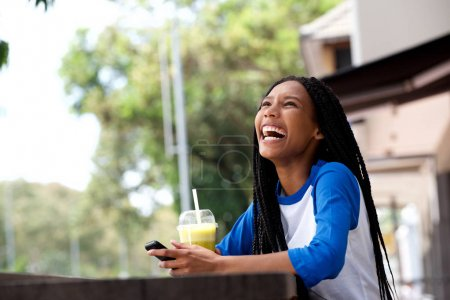 Portrait of happy young african american woman with mobile phone at cafe