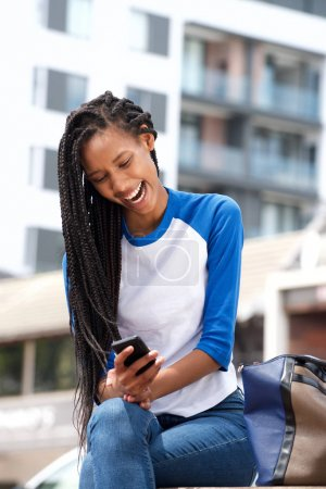 Photo for Portrait of african american girl reading text message on mobile phone outdoors - Royalty Free Image