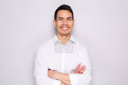 Close up portrait of happy middle aged asian man standing with his arms crossed against gray background