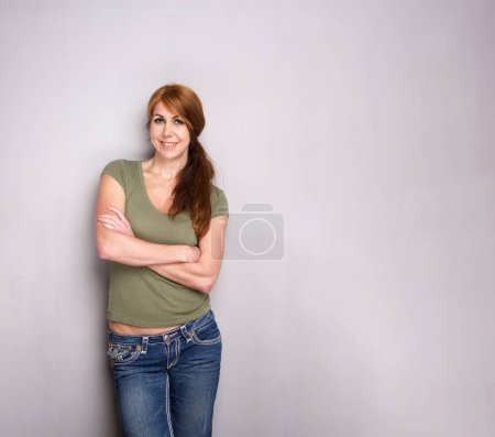 Portrait of beautiful and stylish older woman standing by gray wall with her arms crossed