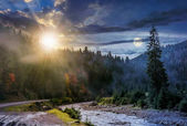 day and night change over foggy forest and river