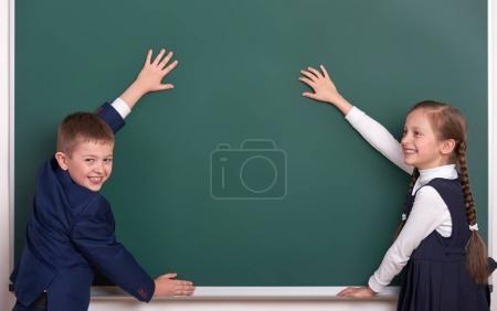Photo pour École primaire garçon et fille mettre la main sur le fond de tableau et montrer l'espace vide, habillé en costume noir classique, élève de groupe, concept d'éducation - image libre de droit