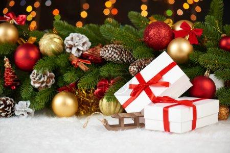 Photo pour Décoration de Noël sur sapin arbre branche closeup, luge en bois de jouets, cadeaux, Noël boule, cône et autre objet sur la fourrure de l'espace blanc, concept de vacances, place pour texte - image libre de droit