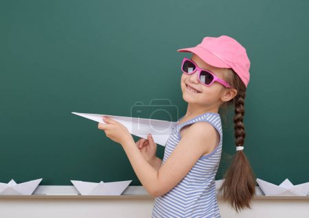 Photo pour Écolière avec avion en papier jouer près d'un tableau noir, espace vide, concept éducatif - image libre de droit