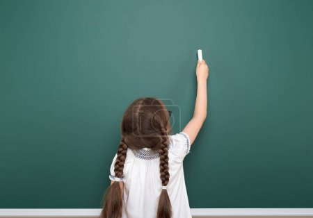 Photo for Schoolgirl writing chalk on a blackboard, empty space, education concept - Royalty Free Image