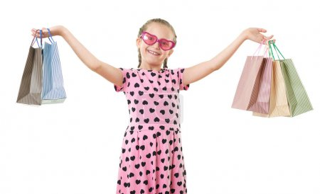 Photo for Pretty little girl with shopping bag, studio portrait, dressed in pink with heart shapes, white background - Royalty Free Image