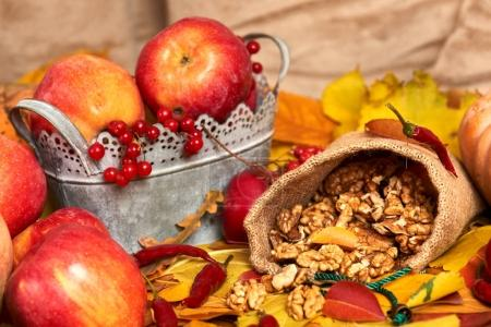 Photo for Nuts in a sack, fruits and vegetables on fallen leaves background, autumn season - Royalty Free Image