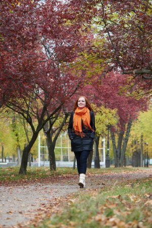 Photo for Young woman walk on footpath in autumn park, yellow leaves and trees - Royalty Free Image