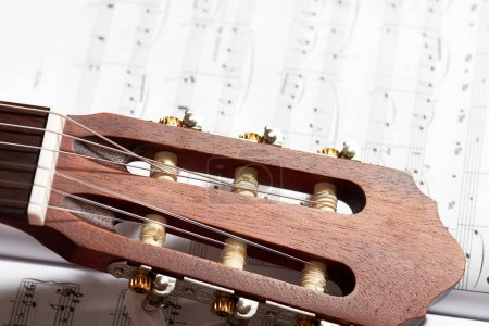 Photo for Closeup of acoustic guitar on music notes - Royalty Free Image