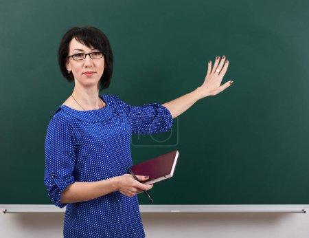 Foto de Profesor de la mujer haciéndose pasar por el tiro de tiza tablero, concepto de aprendizaje, fondo verde, estudio - Imagen libre de derechos