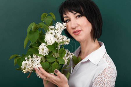 Photo for Portrait of woman with lilac flowers on green blackboard background - Royalty Free Image