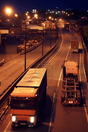 Photo for Truck with container rides on the road, freight cars in industrial seaport at night - Royalty Free Image